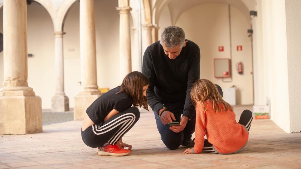L'investigador Josep M. Serra-Grabulosa mostrant NeurekaNUM a dues nenes
